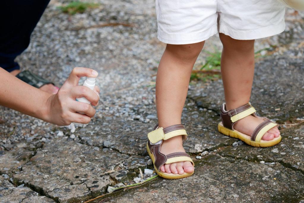 mulher passando repelente em seu filho